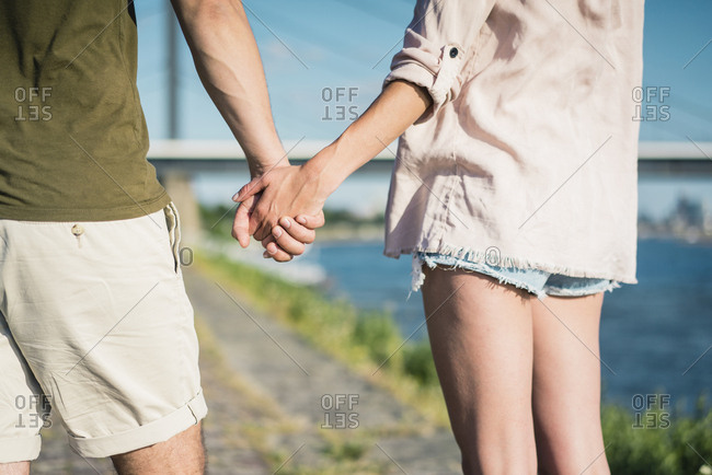 Close-up of couple hand in hand on waterfront promenade in summer