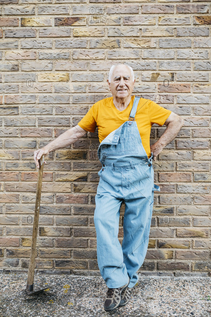 Senior man in denim overall with garden tool looking at camera leaning on a wall