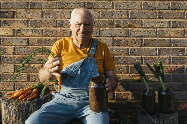 Smiling senior man with glass jars of soil and fresh carrots looking at camera