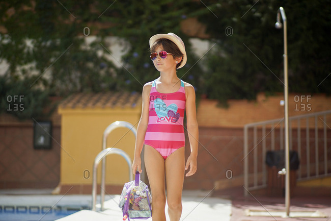 Young girl arriving at the pool in summer with bath clothes