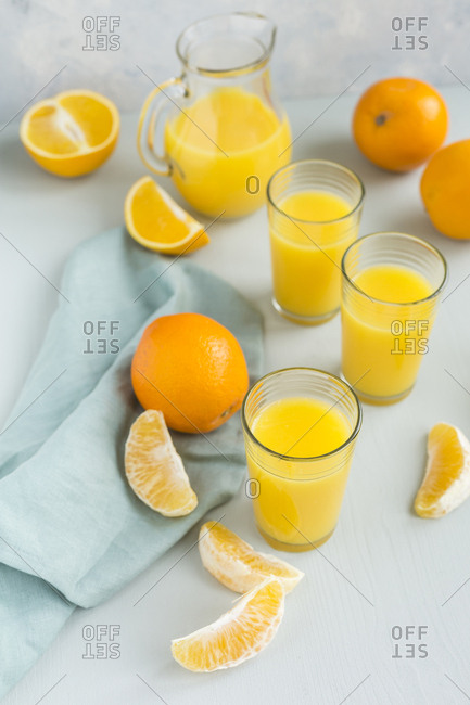 Glasses of freshly squeezed orange juice and oranges