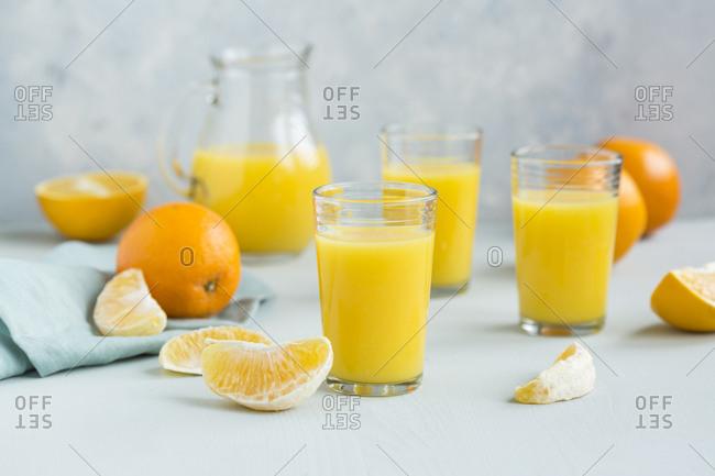 Glasses of freshly squeezed orange juice and orange slices