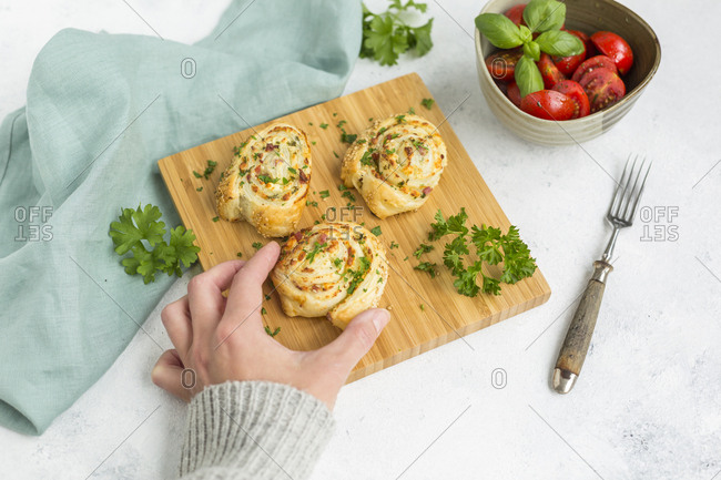 Woman's hand taking sticky bun with feta- cream cheese- bacon and parsley