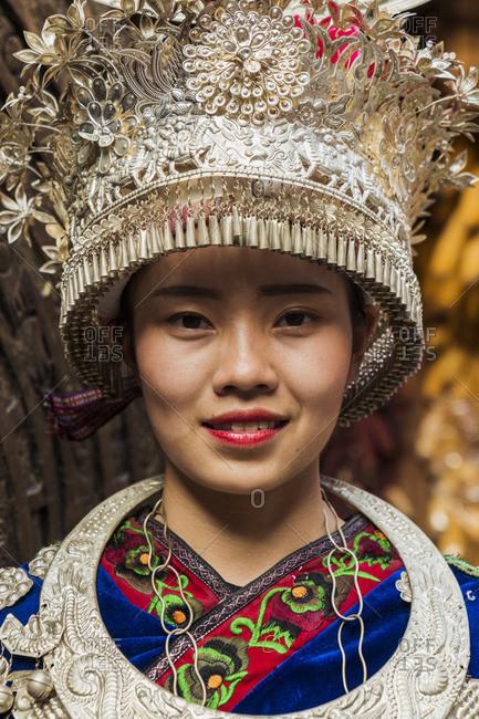 China- Guizhou- portrait of a young Miao woman wearing traditional dress and headdress
