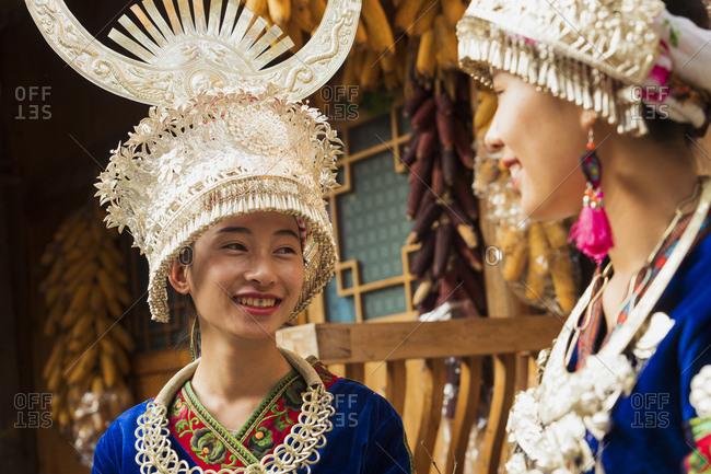 China- Guizhou- two smiling young Miao women wearing traditional dresses and headdresses