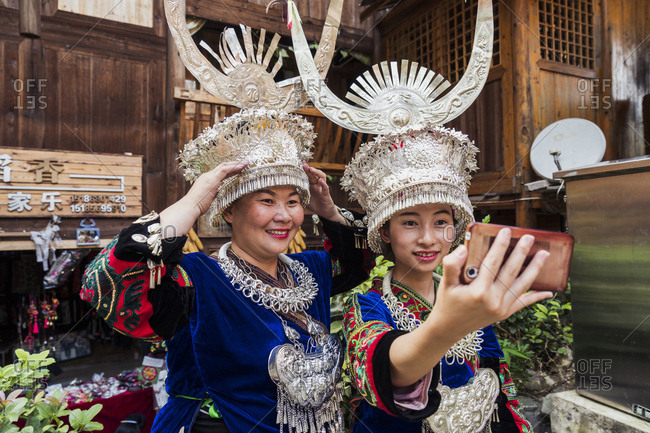 China- Guizhou- two Miao women wearing traditional dresses and headdresses taking a selfie with smartphone