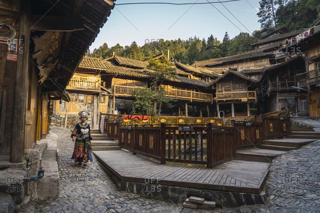 China- Guizhou- young Miao woman in traditional dress walking in a settlement