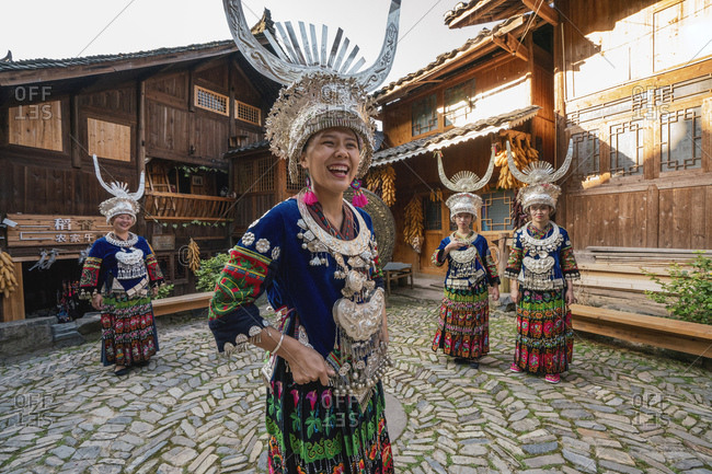 China- Guizhou- happy Miao women wearing traditional dresses and headdresses standing on village square