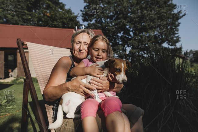 Smiling grandmother with granddaughter and dog on deckchair in garden
