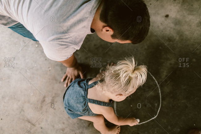 father and daughter drawing with chalk on the sidewalk