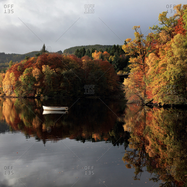 Autumn trees reflecting on a calm Loch Faskally in Perthshire, Scotland