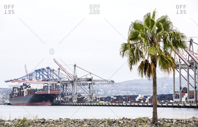 Container ship being loaded with cargo at industrial port