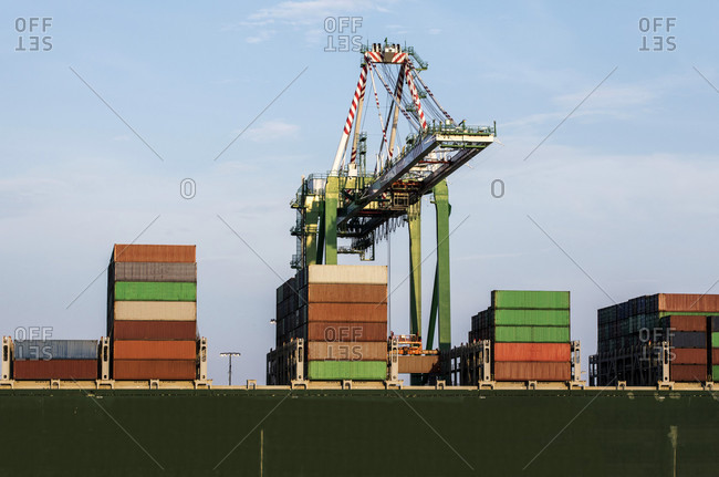 Cargo containers and loading crane at industrial port