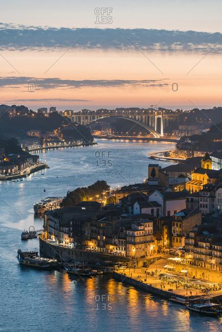 Portugal, Norte region, Porto (Oporto). Douro river banks at dusk with Arrabida bridge in the background.
