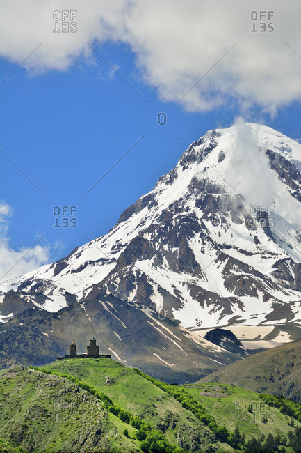 Mount Kazbek (5047m), the third-highest peak in Georgia, bordering Russia, with the Gergeti Trinity Church on its slopes. Khevi-Kazbegi region. Georgia, Caucasus