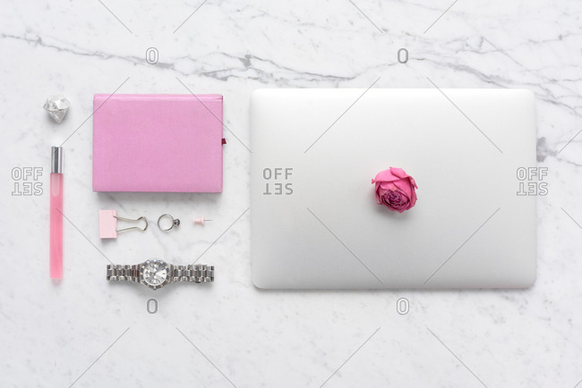 Girly workspace flat lay. Directly above view of female accessories, stationery and laptop with pink dried rose above lying on white marble table