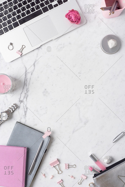 Workplace of romantic girl. Flat lay composition of laptop, pink stationery, cosmetics and dried rose lying on white marble table