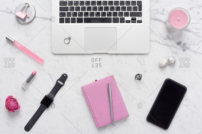 Workplace of glam girl. Creative flat lay composition of laptop, pinkish stationery and accessories lying on white marble table background