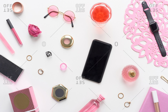 Perfect girly flat lay. Directly above view of pink female accessories, cosmetics and black modern smartphone lying on white table background