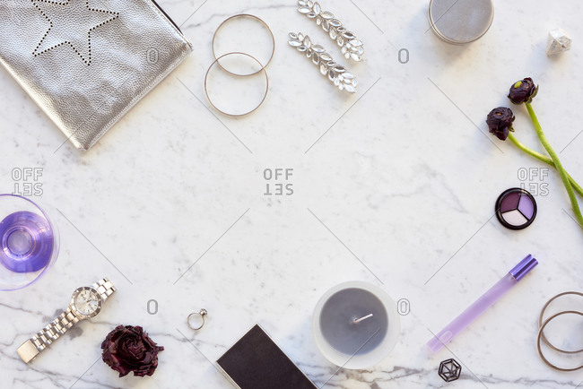 Creative feminine flatlay. Top view of fashionable female accessories, cosmetics, wristwatch, candles and flowers on white marble table background