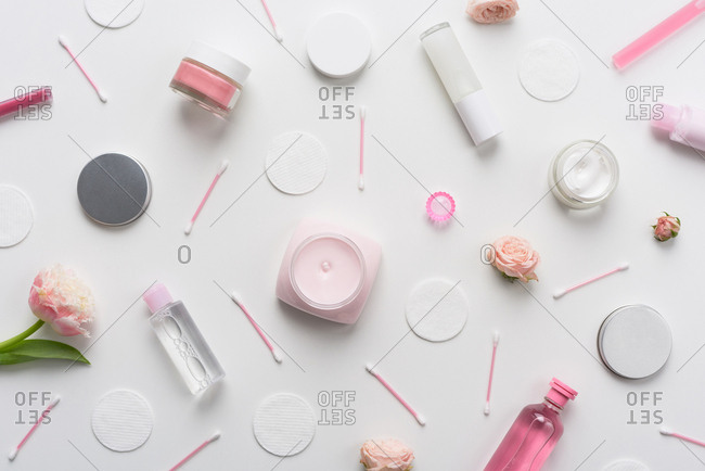 Composition with girlish stuff. Flat lay photo of cream jars, perfume bottles, flowers, cotton swabs and pads lying on white table background