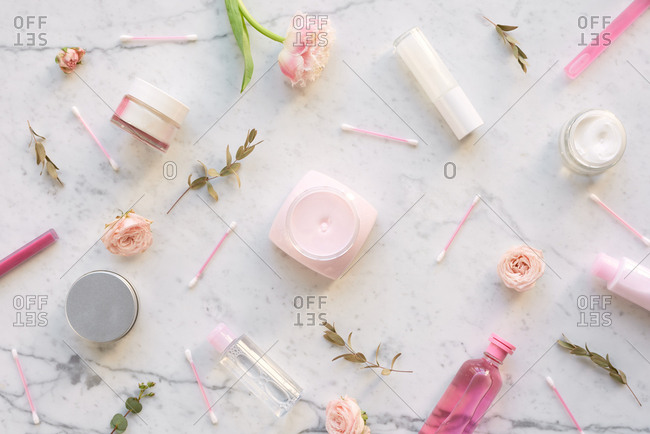 Delicate feminine flatlay. Top view of pinkish bottles and jars with cosmetic, cotton swabs and flowers on white marble table background