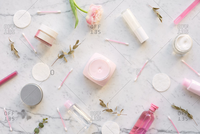 Womanish flatlay with cosmetics. Directly above view of cotton swabs and pads, pink bottles with cosmetics and delicate flowers on white marble table background