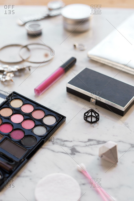 Girly flat lay with cosmetics. Close-up view of eye shadows, lipsticks and trendy female accessories lying on white marble table