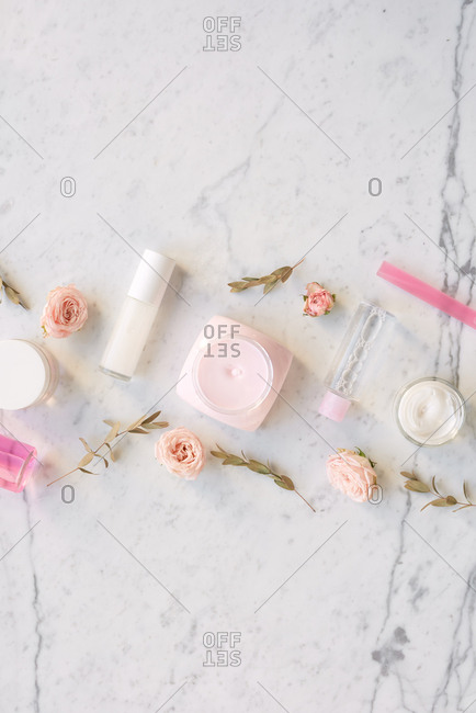 Pretty girlish flat lay. Creative composition of face cream, bottles of perfume and dried pinkish roses lying on white marble table