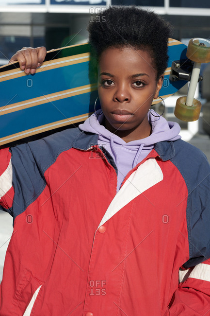 Portrait of young African American woman standing outdoors with longboard and looking at camera with serious face expression