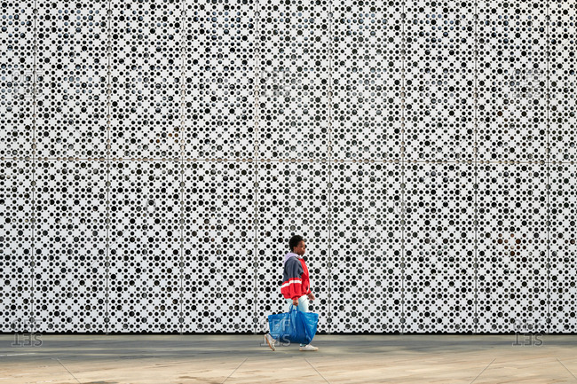 Stylish African American woman with shopping bag walking down the street against modern building with perforated facade