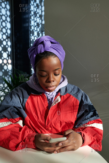 Young black woman in stylish sporty jacket and purple headwrap sitting at cafe  table and texting on smartphone