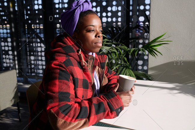 Young stylish black woman holding coffee and looking into the distance dreamily while sitting alone in modern cafe with perforated panels