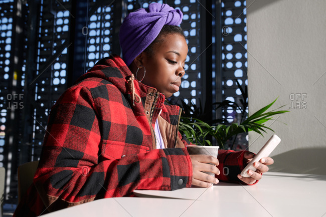 Fashionable African American woman checking social media on smartphone while sitting in modern coffee house with perforated walls, low angle view
