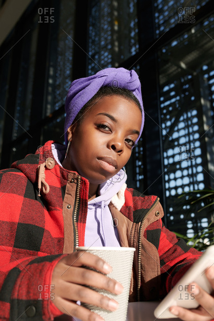 Portrait of young fashionable African American woman looking at camera while sitting in cafe with coffee and smartphone, low angle view