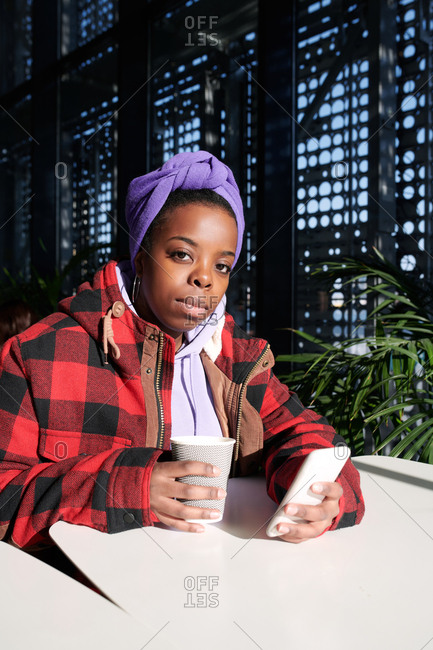 Portrait of young stylish African American woman looking at camera while sitting in modern cafeteria with coffee and smartphone, bright sun illuminating her face