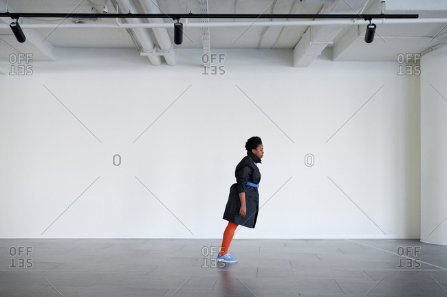 Anti-gravity lean performance. Stylish African American woman doing lean forward in empty parking garage on white wall background, copy space