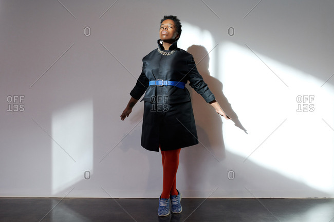 Dreamy woman enjoying sunlight. Stylish black female standing on tiptoes with stretched hands and closed eyes as if flying against white wall with shadows