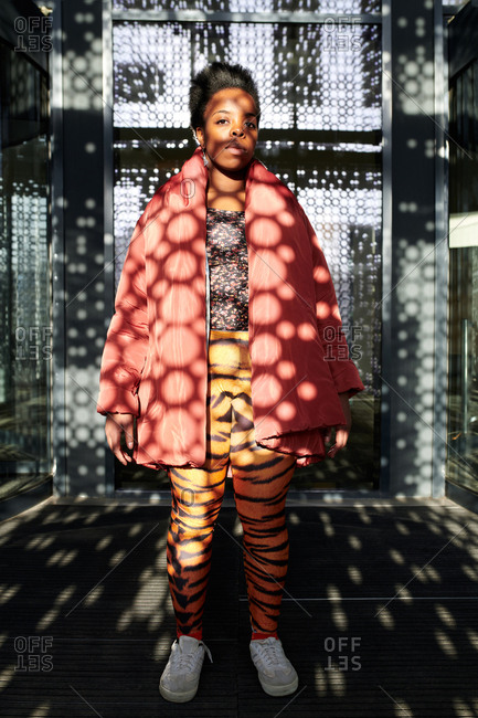 Fashionista in contemporary building. Full-length portrait of young fashionable black woman standing in room with perforated walls and looking at camera
