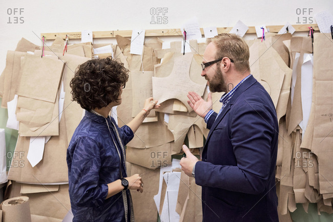 Bearded male tailor and his curly female colleague standing in front of multiple paper patterns in atelier and discussing work