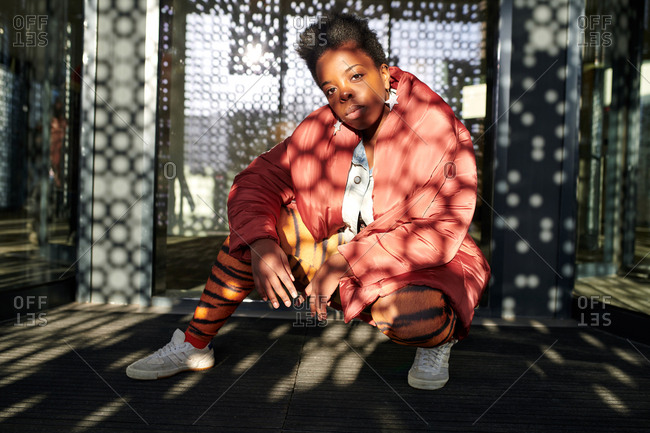 Portrait of attractive black woman in fashionable apparel looking at camera while sitting against entrance doors of contemporary office building