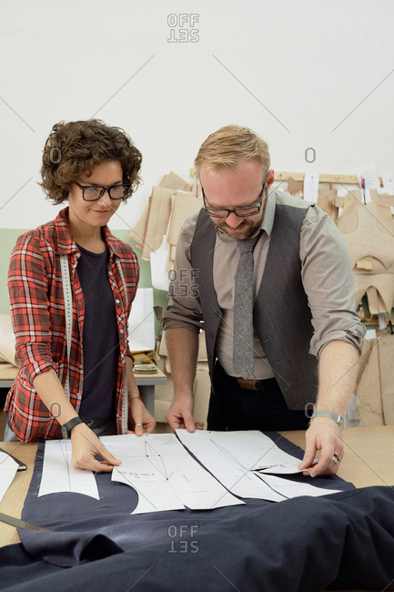 Young enthusiastic female dressmaker and her bearded colleague working together in studio, putting paper patterns on fabric before cutting and sewing