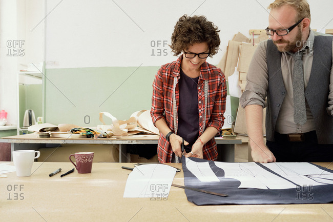 Young female tailor cutting fabric using paper pattern, bearded male colleague standing beside and watching the process