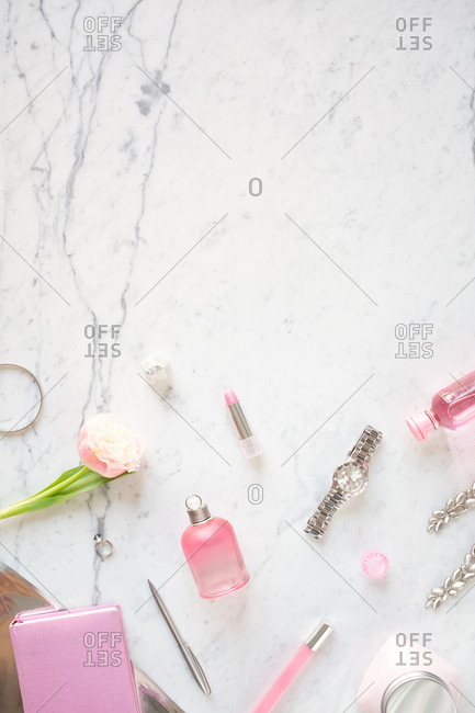 Girly stuff on table. Flat lay composition of perfume, lipstick, wristwatch, pink rose and accessories on white marble table background