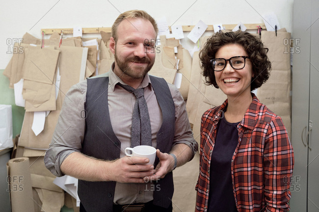Couple running fashion business. Portrait of successful male and female tailors standing in atelier against sewing patterns and smiling at camera cheerfully