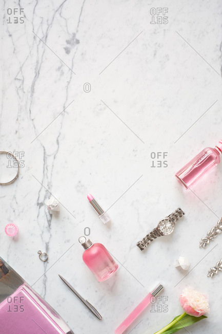 Romantic girlish flat lay. Directly above view of pink perfume bottles, accessories, wristwatch and delicate flower lying on white marble table