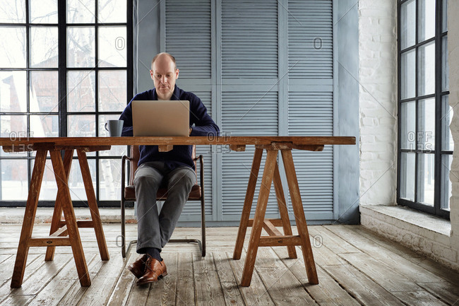 Middle-aged Caucasian businessman sitting at large wooden table and working on laptop in urban cafe with stylish minimalistic interior