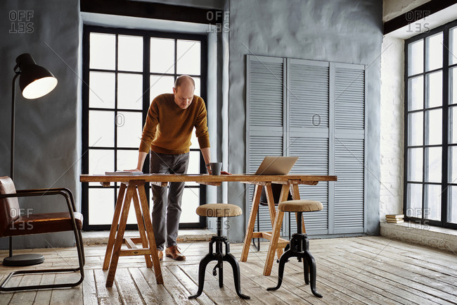 Middle-aged bald male entrepreneur thinking over new project while standing by wooden table in bright vintage office