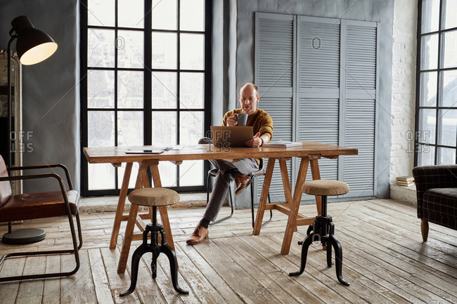 Middle-aged Caucasian businessman reading news on laptop and drinking coffee while sitting at wooden table in vintage office