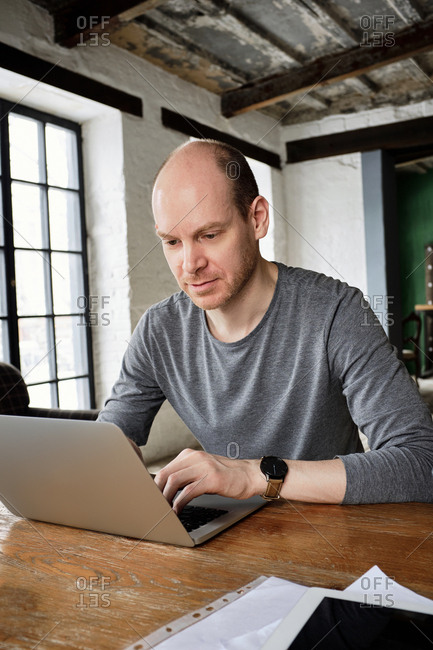 Freelancer working from vintage cafe. Middle-aged bald Caucasian man in gray long sleeve shirt working on laptop while sitting at wooden table